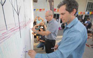 """האמן צ'רלס אייברי וראש העירייה, איציק ברוורמן בציור קיר המשותף עם ילדי המתנ""""סים אחדות ושערים. צילום לשכת דובר העירייה"""