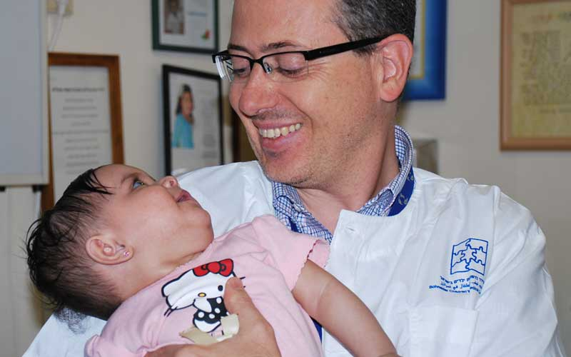 """ד""""ר אורי אלבז והתינוקת. צילום באדיבות מרכז שניידר לרפואת ילדים"""