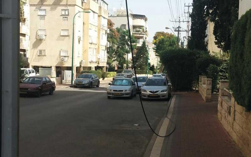 כבל חשמלי על המדרכה ברחוב ביאליק בפתח תקווה
