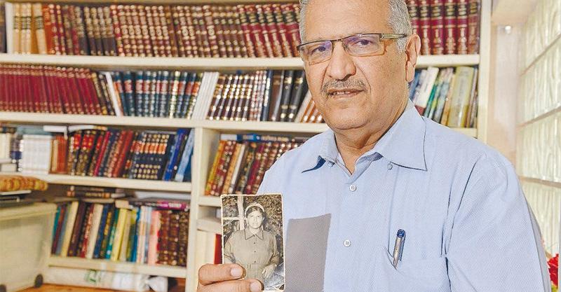 יגאל יוסף מחזיק תמונה של אמו צילום אילן חתוכה