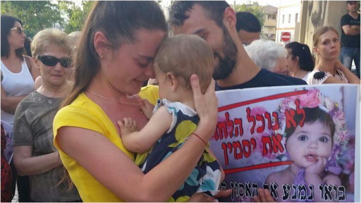 """אמה של יסמין וינטה ז""""ל מחזיקה תינוקת של אחת המשתתפות בהפגנה"""