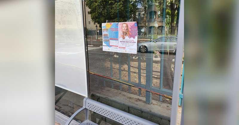 מודעות עירייה על גבי תחנת אוטובוס במנחם בגין